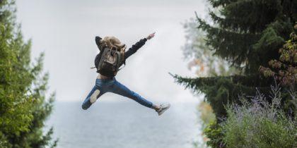 Ryggsidan på en flicka som gör ett glädjehopp på en strand med horisonten som bakgrund
