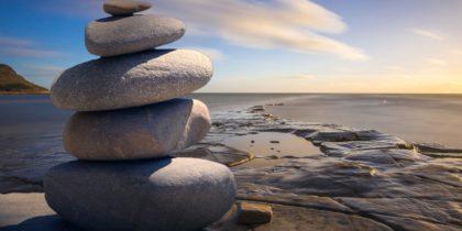 Stenar på hög på en klippa med hav i bakgrunden