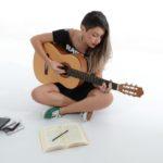 tjej som sitter och spelar gitarr mot helvit bakgrund