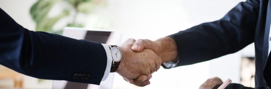 Två kostymklädda armar som skakar hand