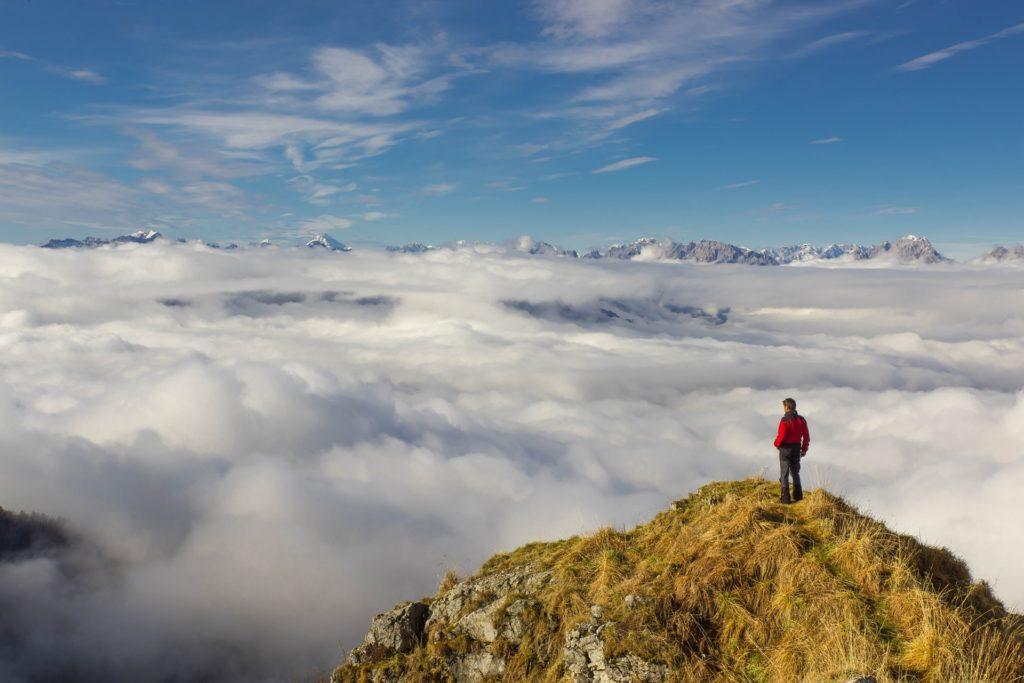 Man på bergstopp blickar ut över molnen