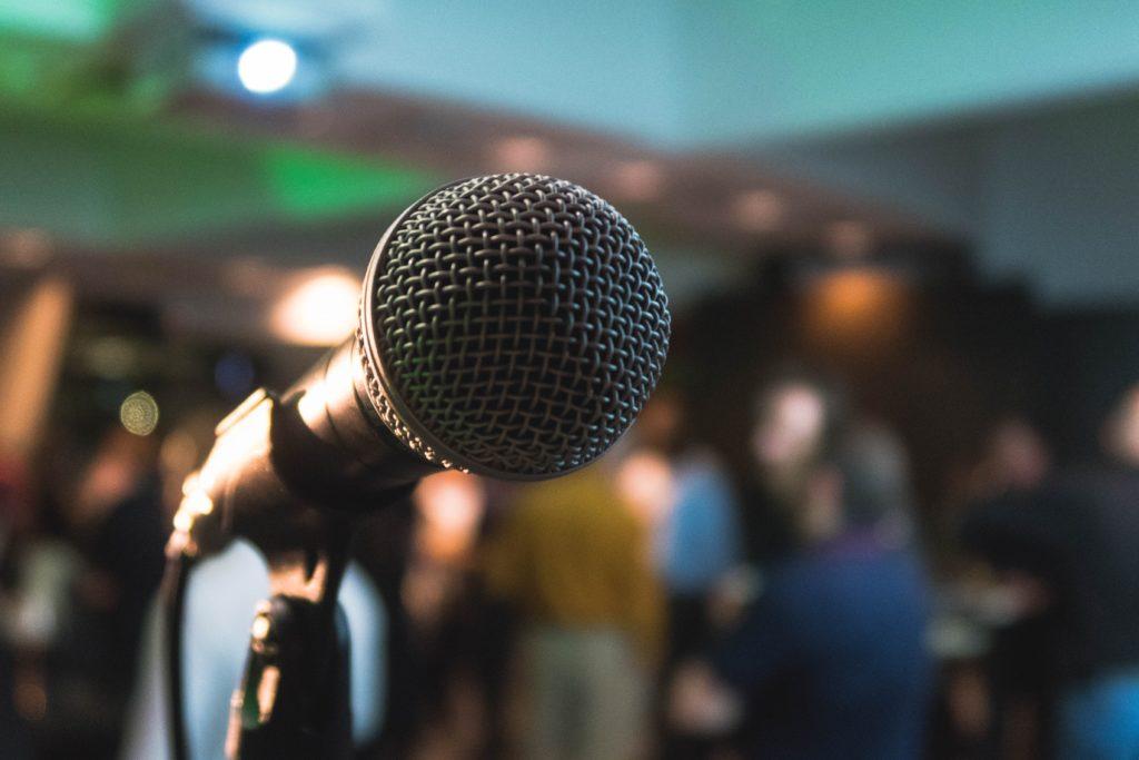 En talarmikrofon i närbild och publik i bakgrunden